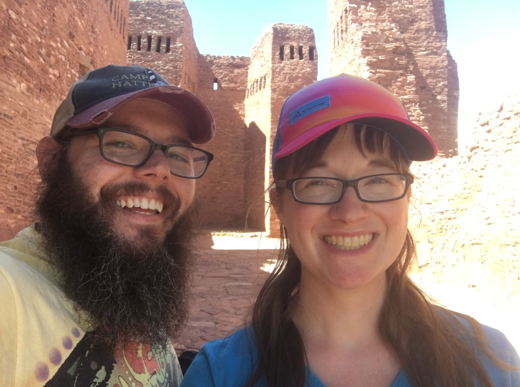 Smiling white woman with bangs and glasses, wearing a baseball cap with blues, pinks, oranges and purples, stands in front of ancient ruins in New Mexico.