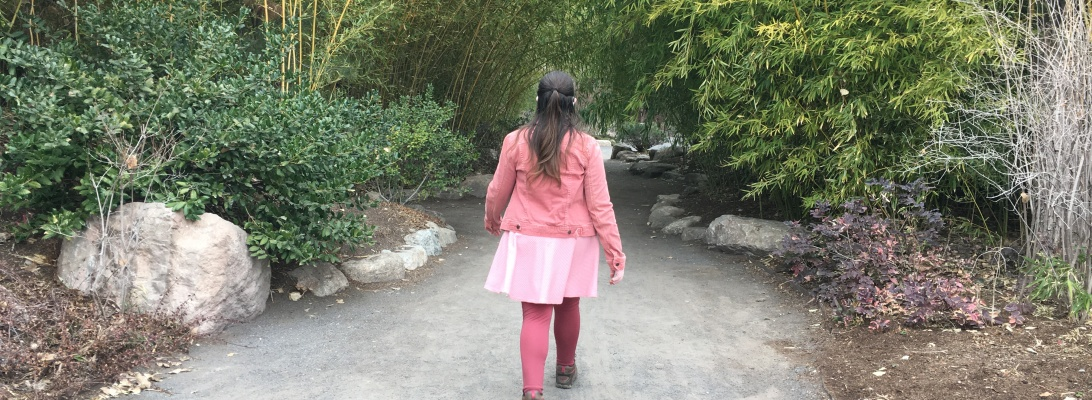 Woman in shades of pink walks forward into a canopy of trees